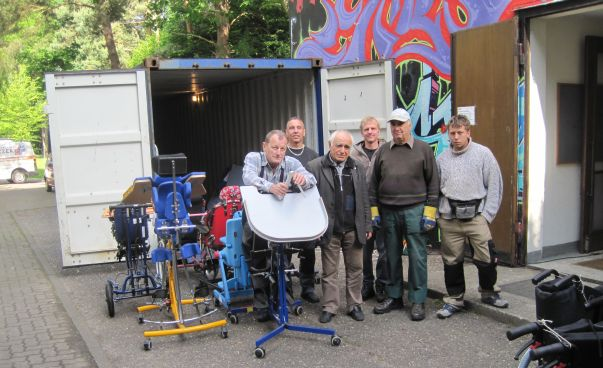 The picture shows a group of men who stand in front of a truck with medical devices.