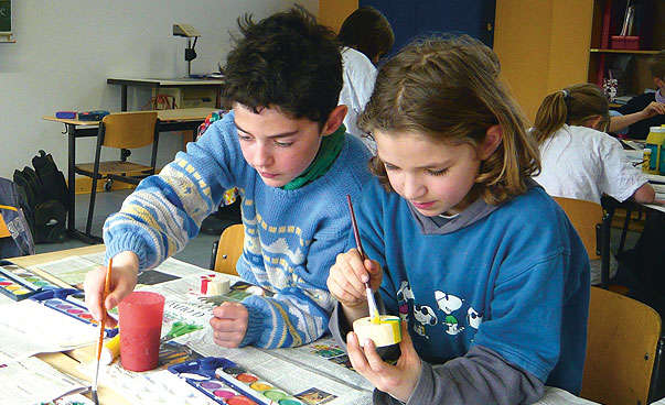A little girl and a boy are painting in school.