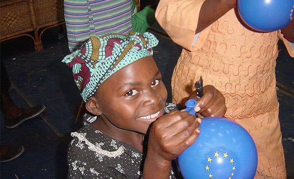An African girl is inflating a balloon.