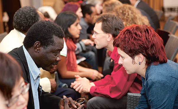 An African Man and a white woman with short red hair are sitting in front of each other and talking between lots of other people.
